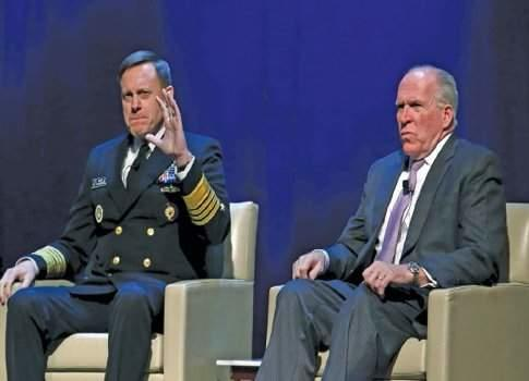 Admiral Michael Rogers, director of U.S. National Security Agency (NSA), gestures next to CIA Director John Brennan during a conference on national security in Washington