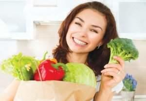 Happy Young Woman with vegetables in shopping bag . Beauty Girl