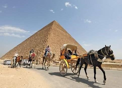 Tourists ride in horse carts in the Giza pyramids area, on the outskirts of Cairo