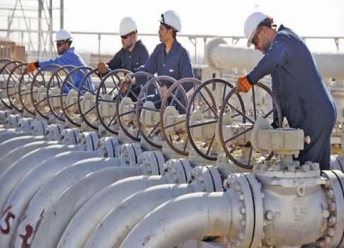 Workers adjust the valves of oil pipes at West Qurna oilfield in Iraq's southern province of Basra