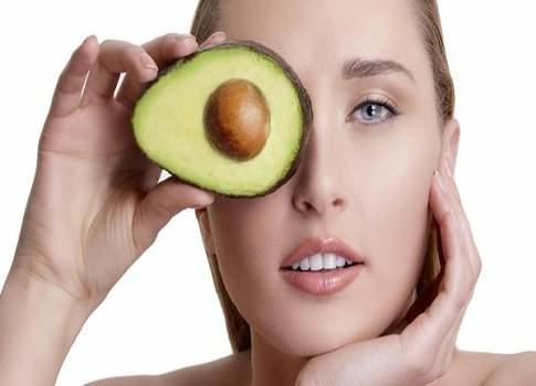 young happy woman showing an avocado